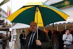 Andreas Tiedtke mit Cheltenham-Regenschirm im Portrait. www.galoppfoto.de