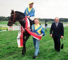 Der Kölner Europa-Preis gewann Monsun gleich zweimal. Auf dem Foto sieht man ihn mit Andrzej Tylicki im Sattel und Trainer Heinz Jentzsch auf dem Kölner Geläuf nach dem Erfolg im Jahr 1994. Foto www.galoppfoto.de - Frank Sorge
