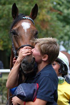 Erlian wird von seiner Pflegerin nach dem Kölner Sieg 2012 geküsst. www.galoppfoto.de - Frank Sorge
