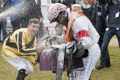 Jockey Eduardo Pedroza bekommt von Jockey Michael Cadeddu eine Sektdusche nach dem Sieg im IDEE 150. Deutschen Derby mit Laccario. www.galoppfoto.de