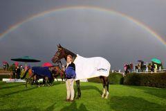 Sarandia mit Pflegerin nach dem Sieg unter einem Regenbogen. www.galoppfoto.de - Marius Schwarz