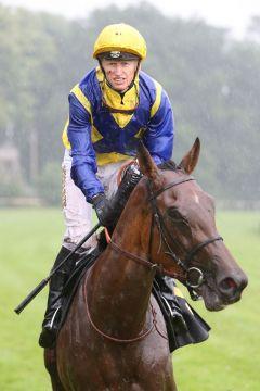 Wetter schlecht, Laune gut: Filip Minarik auf Well Timed. www.galoppfoto.de